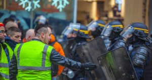 yellow vest protestor facing police officers