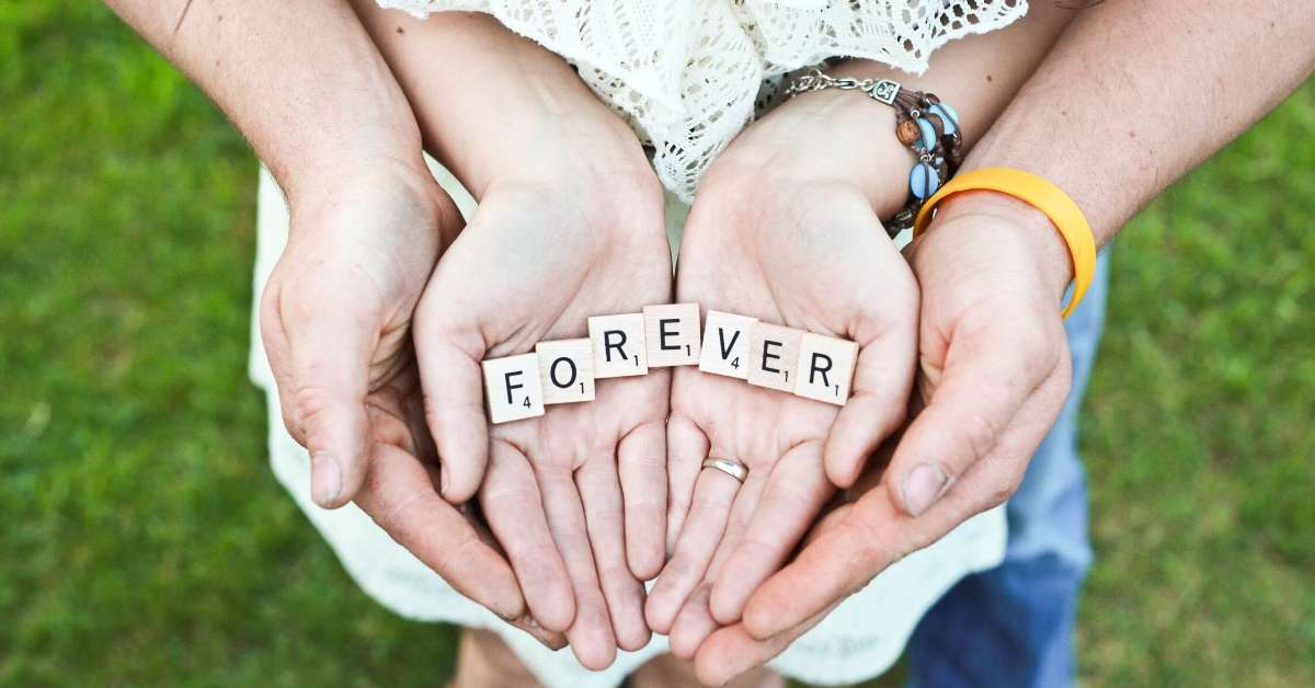 Man and woman hand-holding with the words forever written with Scrabble tiles: honeymoon in Provence episode