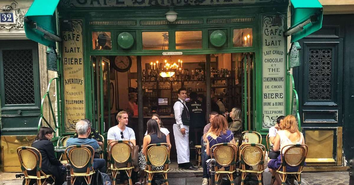Café in Paris with people sitting outside and waiter looking at the camera