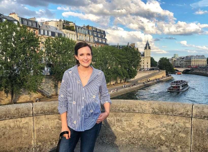 Lauren standing on a bridge in Paris: solo in Paris episode