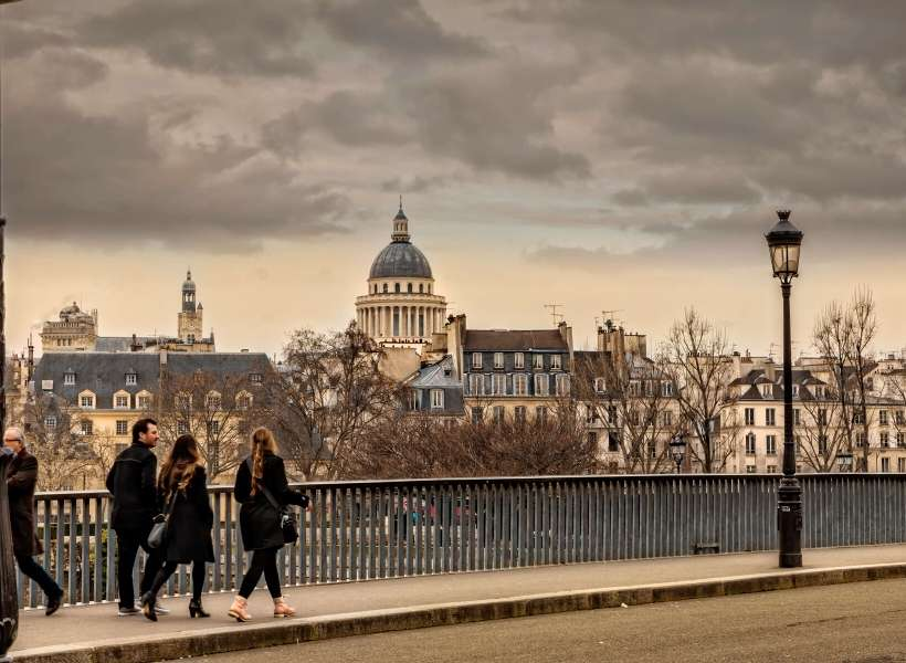Visitors walking on a bridge in Paris: tours make a vacation better episode