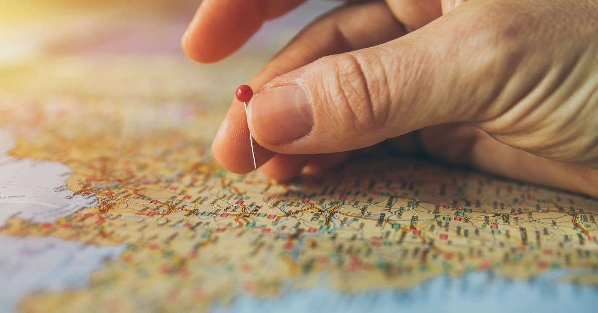 Woman placing a pin on a map: Best Practices When Preparing a Trip to France episode