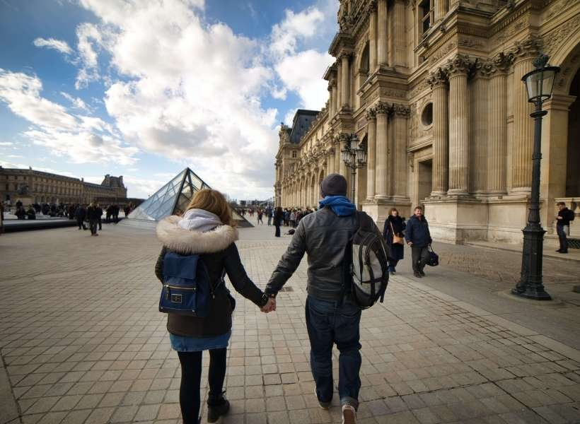 Man and woman holding hands walking towards the Louvre Museum: Best Practices When Preparing a Trip to France episode