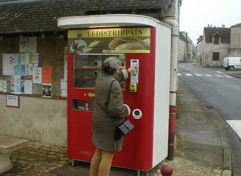 Susan buying bread from a bread vending machine